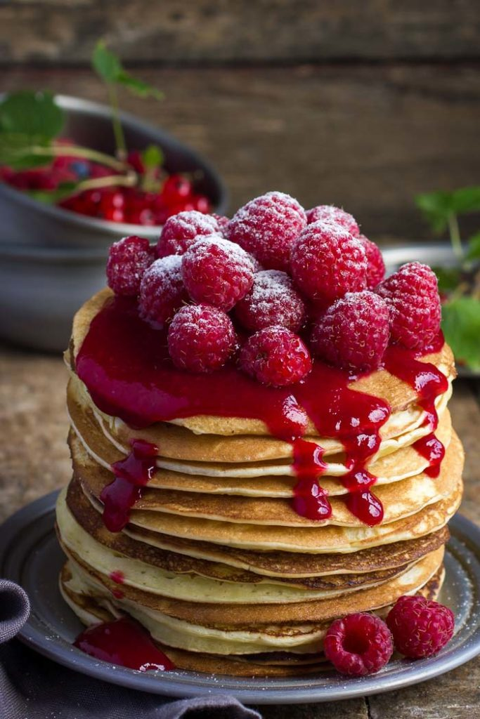 A stack of raspberry almond flour pancakes topped with fresh raspberries as pancake toppings