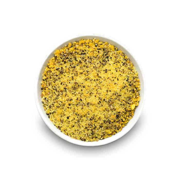 a white dish of lemon pepper seasoning on a white background