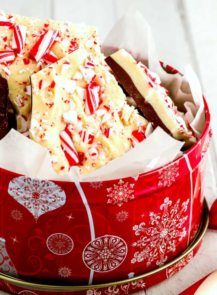 Homemade chocolate peppermint bark in decorative tin with candy cane