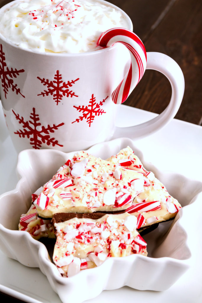 Snowflake mug of hot cocoa and festive bowl filled with chocolate peppermint bark