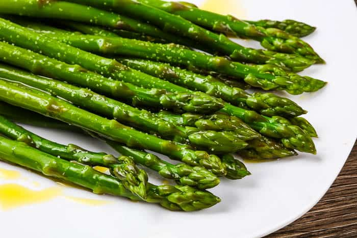 oven roasted asparagus on a white plate with salt and olive oil