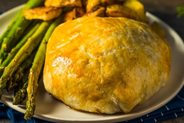 An individual chicken wellington on a light brown plate with asparagus and crispy potatoes