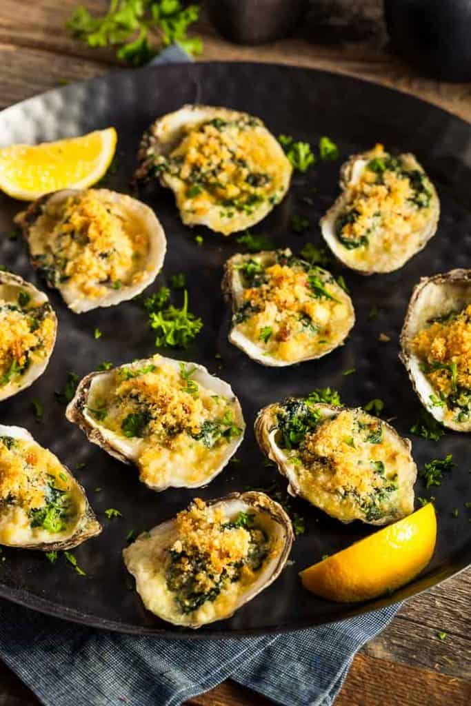 a platter of oysters rockefeller with lemon wedges as a garnish