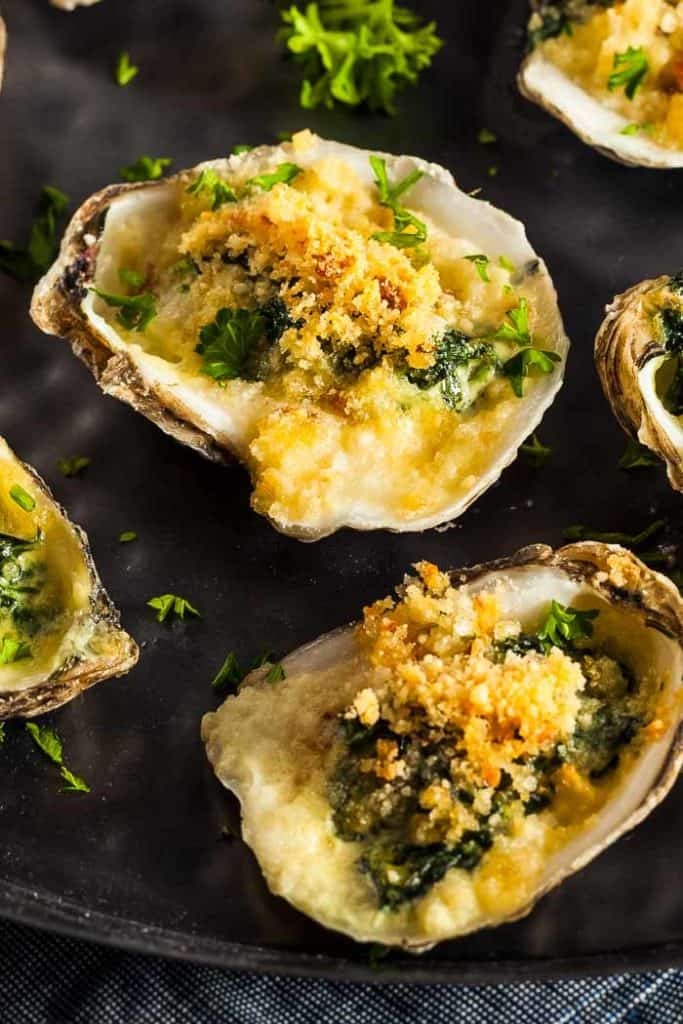 oysters rockefeller on a black plate with fresh parsely