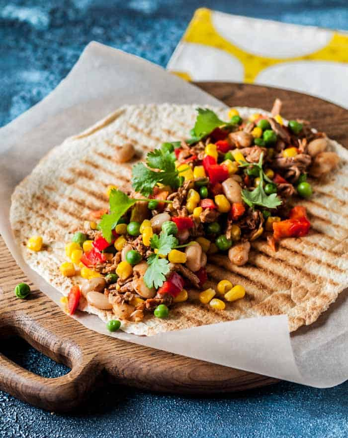 Pulled pork and grilled, chopped vegetables on a tortilla that's set on a round wooden board