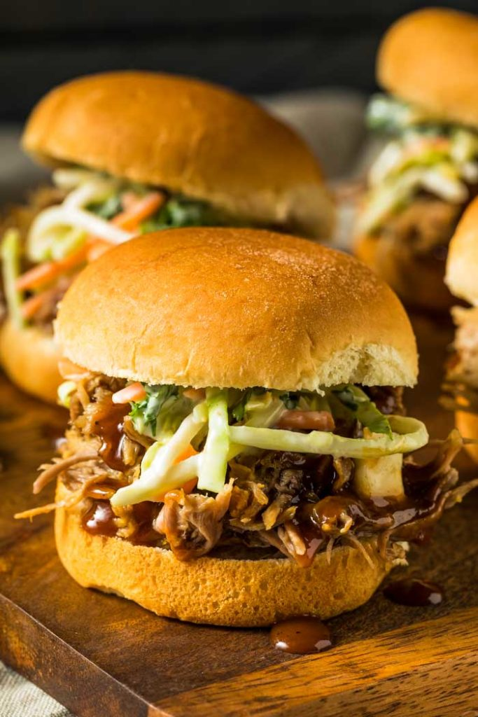 A photo of pulled pork sliders with coleslaw on a cutting board