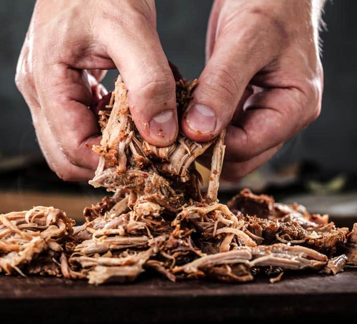 An example of pulling pork with your hands: pulled pork on a cutting board with a man's hands pulling apart a large piece of pork