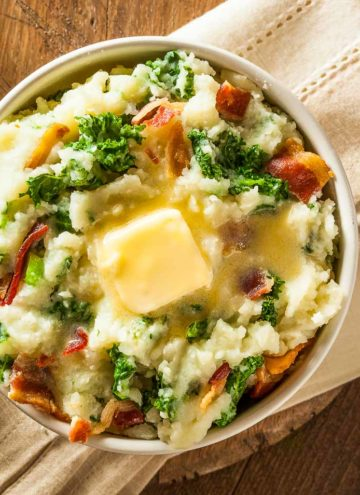 A bowl of colcannon on a tan napkin over a wood table