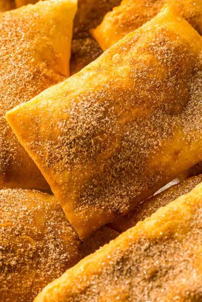 sopapillas from a new mexico sopapilla recipe sprinkled with cinnamon just out of the fryer