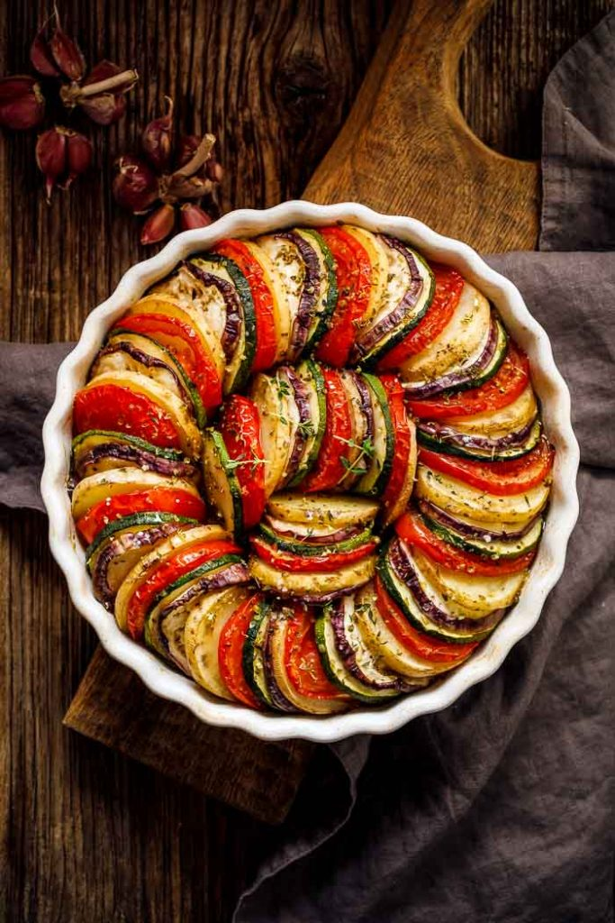 A summer vegetable tian closeup before baking in a round dish