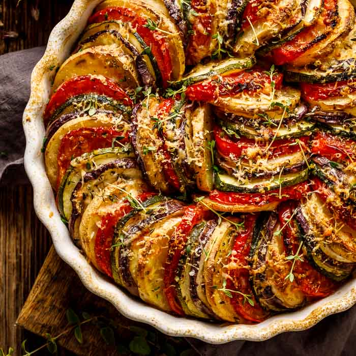 A vegetable tian closeup just after baking in a round white dish