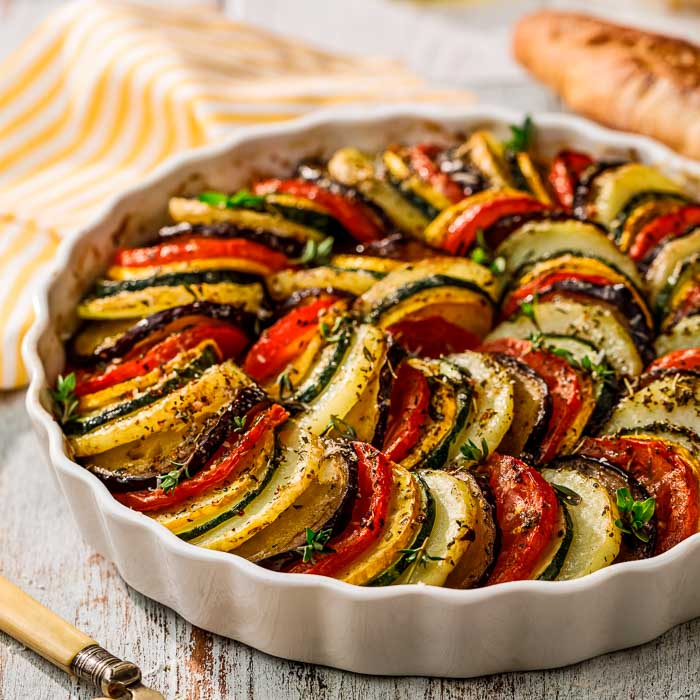 A vegetable tian just after baking in a round white dish on a white table with a striped yellow and white napkin
