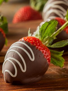 semi-sweet chocolate covered strawberries drizzled with white chocolate on a wooden board