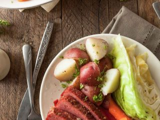 A plate of corned beef and cabbage with potatoes and carrots on a wooden table with a fork and knife