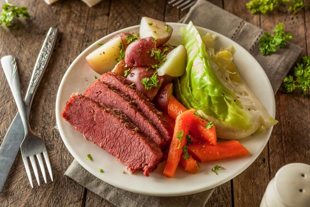 A plate of corned beef and cabbage with potatoes and carrots on a wooden table and a beige napkin