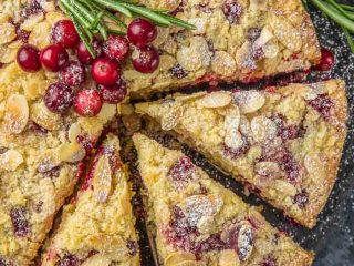 a closeup of cranberry christmas cake topped with fresh cranberries and a sprig of fresh rosemary