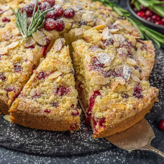 cranberry christmas cake topped with fresh cranberries and a sprig of fresh rosemary