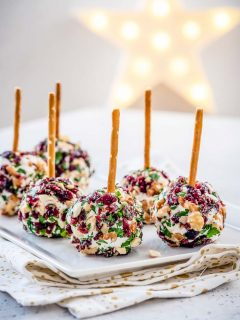 cranberry cheese balls on a white plate with a gorgeous star in the background