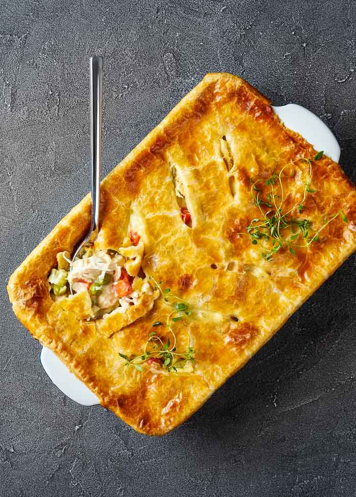 instant pot chicken pot pie baked in a white casserole dish on a grey background