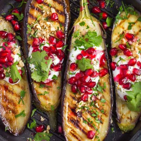 a closeup of grilled eggplant topped with garlic yogurt sauce, walnuts and pomegranate