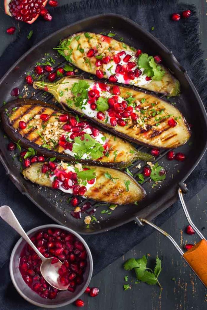 grilled eggplant topped with garlic yogurt sauce, walnuts and pomegranate with a small dish of pomegranate arils and a spoon next to it