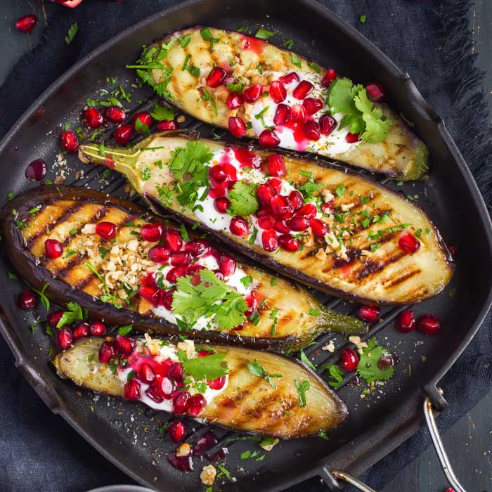 grilled eggplant topped with garlic yogurt sauce, walnuts, pomegranate, and chopped cilantro