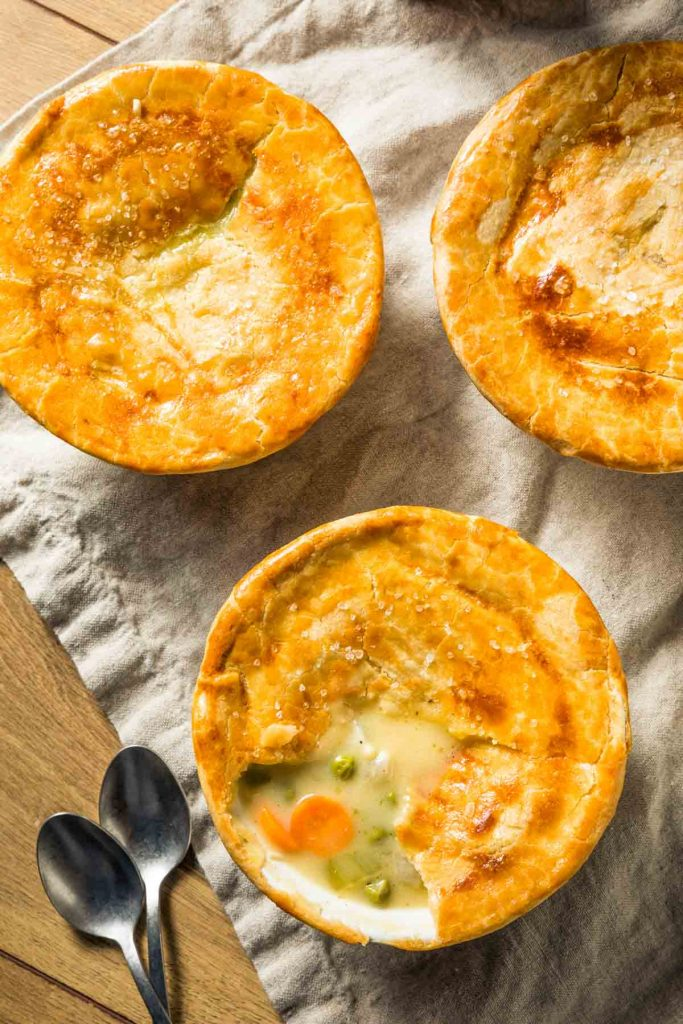 individual instant pot chicken pot pies on a beige napkin with two spoons