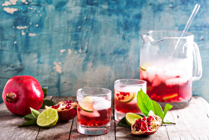 A pitcher of pomegranate margaritas with a whole pomegranate, half a lime, and two glasses on a wooden board with a blue background