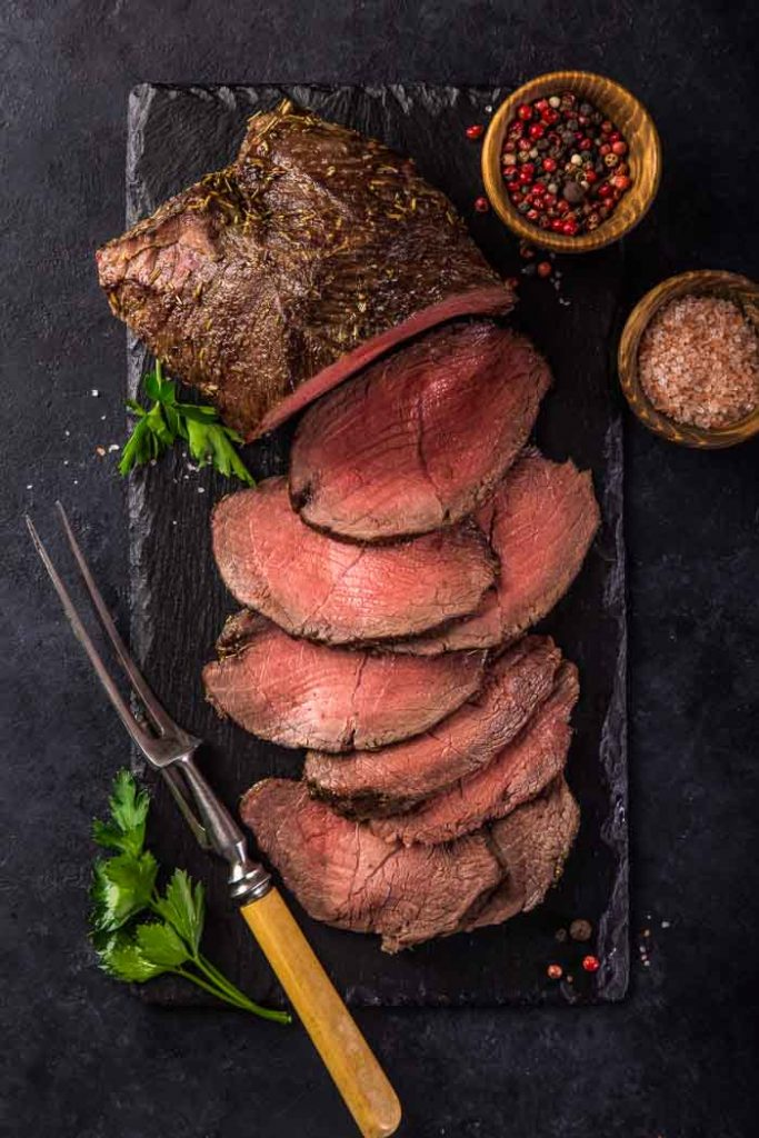 a beef roast with sliced roast beef next to it on a black plank with a small dish of each salt and peppercorns