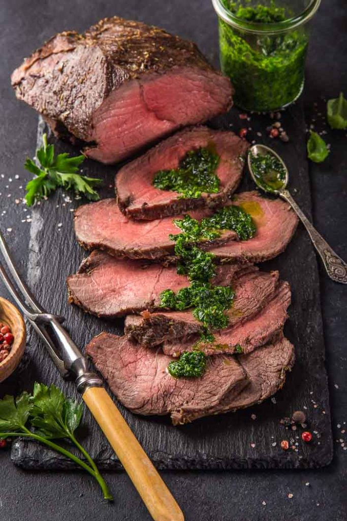 a beef roast with sliced roast beef next to it that's coated in cilantro chimichurri on a black plank