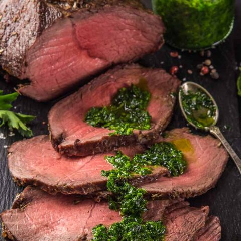 a closeup of a beef roast with sliced roast beef next to it that's coated in cilantro chimichurri on a black plank
