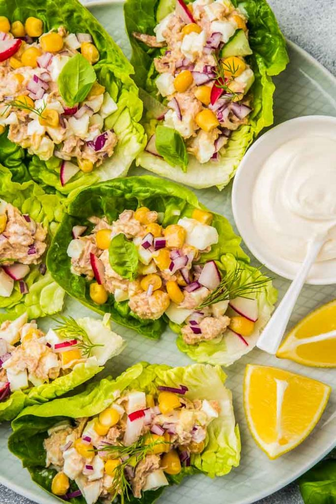 a closeup of tuna salad lettuce wraps with a small dish of mayo and lemon wedges