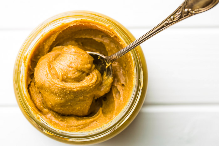 a jar of keto peanut butter on a white table