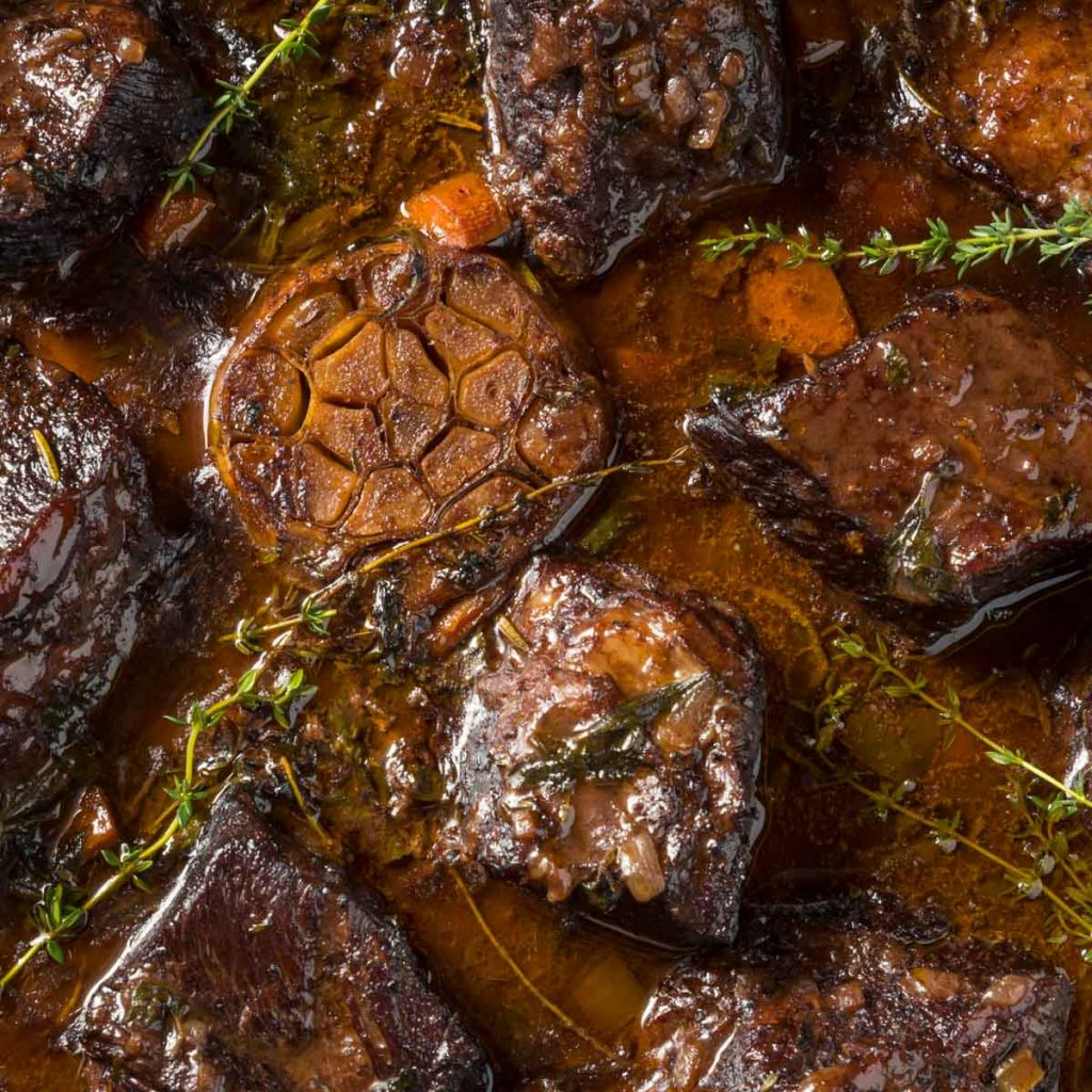 a closeup of a pot of braised beef short ribs