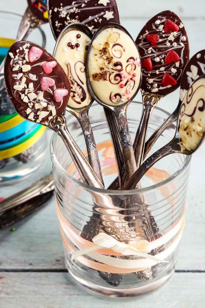 chocolate spoons with sprinkles, nuts, and hearts, set in a glass tied with ribbon