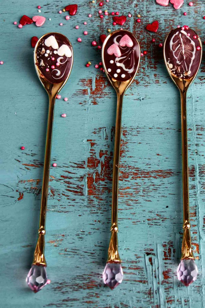 a set of three chocolate spoons with long handles on a teal tabletop