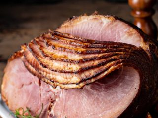 a spiral sliced ham on a white plate with fresh orange wedges on a wood table