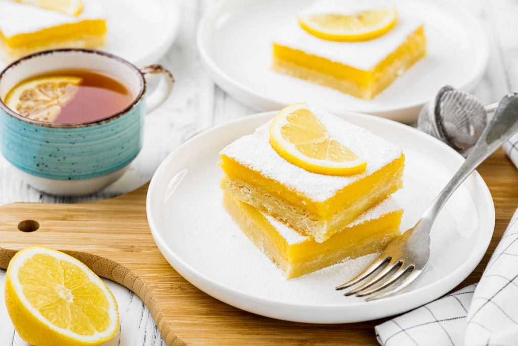 two lemon bars on a white plate next to a cup of tea