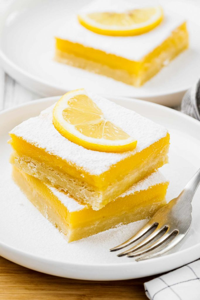 a stack of two lemon bars on a white plate with a silver fork