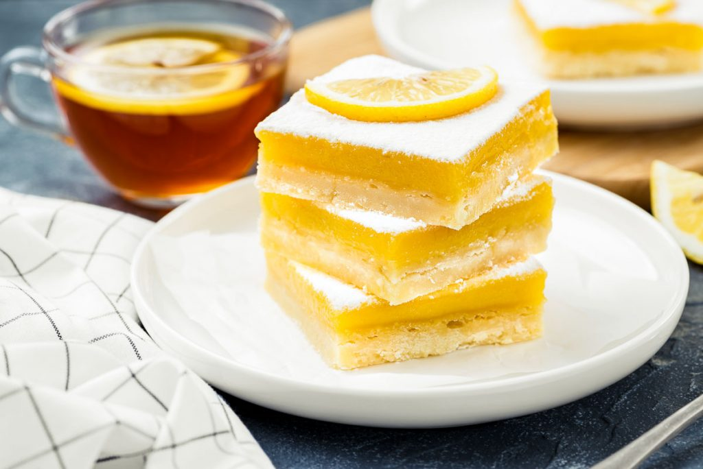 a stack of three lemon bars next to a cup of tea