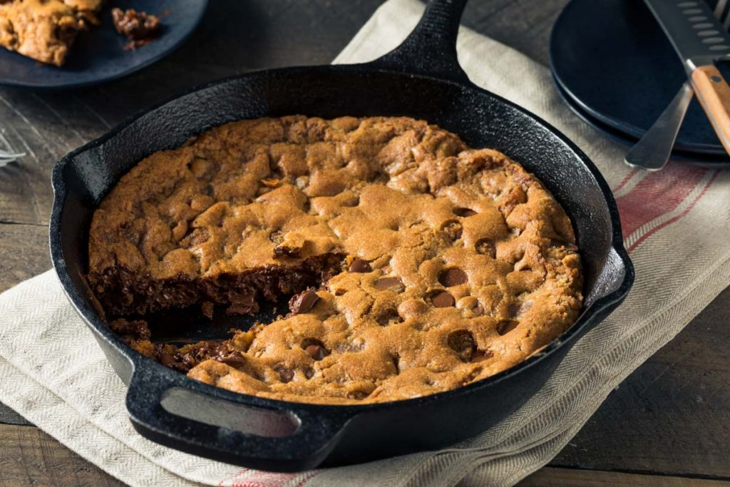 a skillet cookie in a cast iron pan just out of the oven with one piece removed