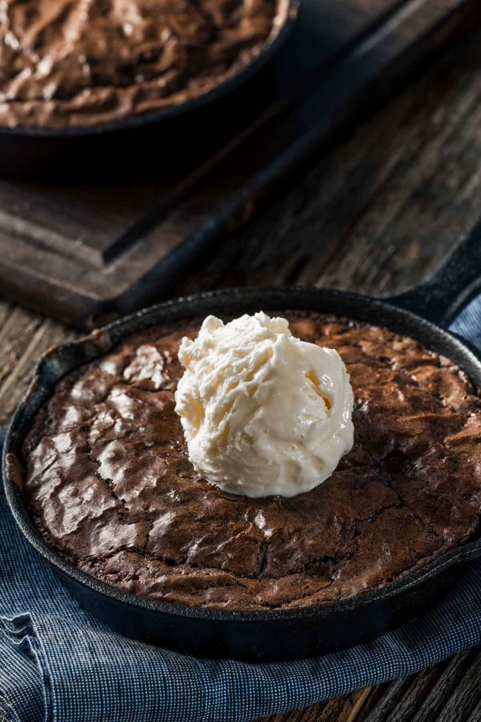 a pan of cast iron skillet brownies with a scoop of vanilla ice cream on a wood table
