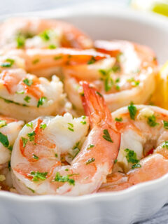 a closeup of garlic butter shrimp scampi in a white bowl