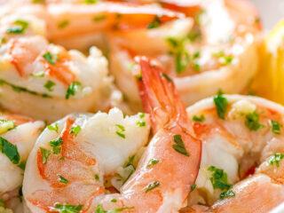a closeup of garlic butter shrimp scampi in a white bowl