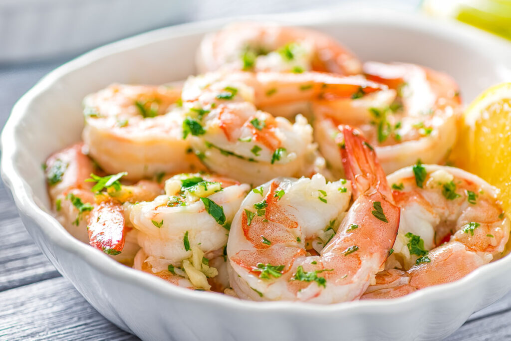 garlic butter shrimp scampi in a white bowl with a lemon wedge