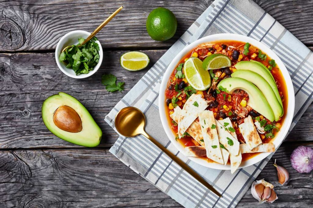 a bowl of taco soup topped with homemade tortilla chips, avocado slices, and fresh lime wedges