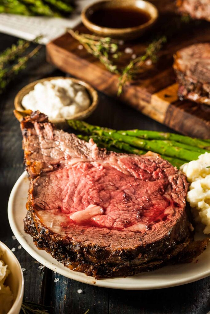 a slice of prime rib with garlic peppercorn wet rub on a plate with mashed potatoes and roasted asparagus