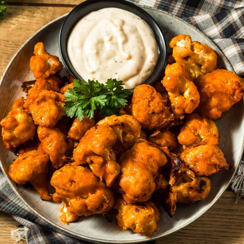 a plate of buffalo cauliflower wings with a small dish of ranch dressing next to a plaid towel