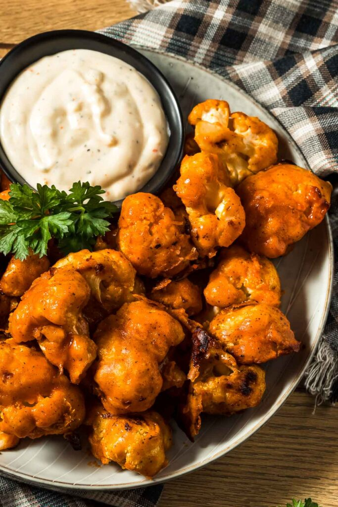 a closeup of a plate of buffalo cauliflower wings with a small dish of ranch dressing next to a plaid towel