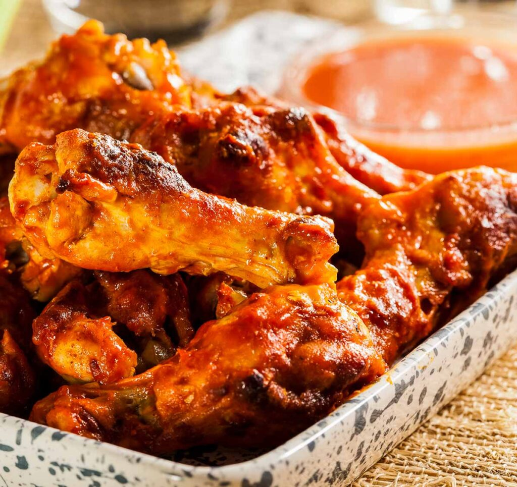 a plate of wings tossed with keto buffalo sauce